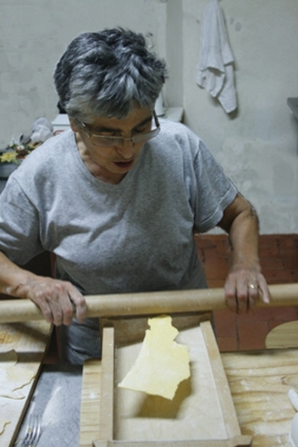 Toskanische Köchin rollt Nudeln